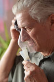 Close-up of an old man doing inhalation — Stock Photo