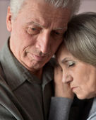Sad elder couple on brown background — Stok fotoğraf
