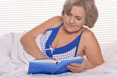 Older woman resting in the bedroom — Stock Photo