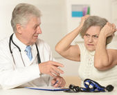 Caucasian aged doctor with a elderly patient — Stock Photo