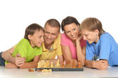 Happy family playing chess — Stock Photo