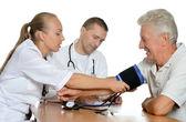Young nurse measuring blood pressure — Photo