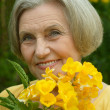 Senior woman with yellow flowers — Stock Photo