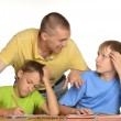 Kids doing homework with father — Stock Photo