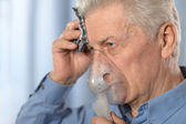Close-up portrait of an elder man making inhalation — Stock Photo