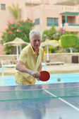 Elderly man playing ping pong — Stock Photo