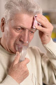 Elderly man making inhalation — Stock Photo