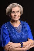 Elderly woman on black background — Stock Photo