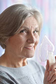 Elderly woman doing inhalation — Stock Photo