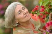 Mulher mais velha com flores — Fotografia Stock