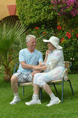 Senior couple sitting at tropic hotel garden — Stockfoto