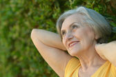 Happy elderly woman in park — Photo