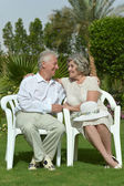 Senior couple sitting at tropic hotel garden — Stock Photo