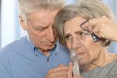 Elderly couple with inhaler — Stock Photo
