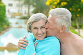 Amusing elderly couple in pool — Stock Photo
