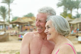 Amusing elderly couple on a beach — Stock Photo