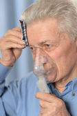 Elder man making inhalation — Stockfoto