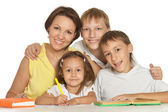 Mother doing homework with her children — Stock Photo