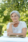 Senior woman in summer at table — Stock Photo
