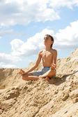 Junge sitzt auf einem felsen — Stockfoto