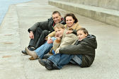 Family of four sitting at river embankment — Stockfoto