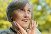 Happy senior woman in autumn park — Stock Photo