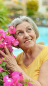 Older woman with flowers — Stock Photo