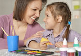Mother and little girl painting — Stock Photo