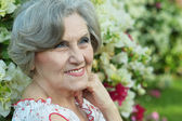 Older woman with white flowers — Stock Photo