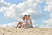 Happy family sitting on a sand — Stock Photo