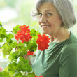 Senior woman with red flowers — Stock Photo #46719935