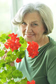 Senior woman with red flowers — Photo