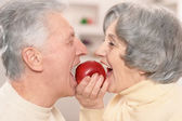 Senior couple eating apple — Stock Photo