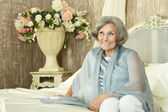 Elderly woman on the couch — Stock Photo