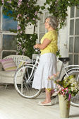 Elderly woman with bicycle — Stock Photo