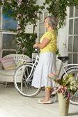Äldre kvinna med cykel — Stockfoto