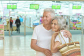 Elderly couple in shopping mall — Stock Photo