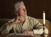 Elderly man reading newspaper — Stock Photo