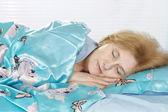 Happy elderly woman in bed — Stock Photo