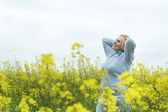 Beautiful old woman in yellow field — Stock Photo