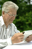Attractive older man reading newspaper — Stock Photo