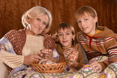 Senior woman knitting with grandsons — Stock fotografie