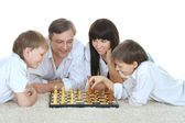 Happy family  playing chess — Stok fotoğraf