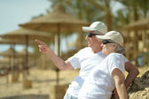Elderly couple having rest on beach — Stock Photo