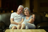 Old couple resting in hotel hall — Stock Photo
