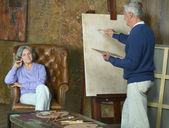 Elderly couple painting with easel — Stock Photo