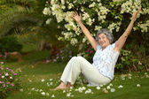 Older woman sitting with flowers — Stock Photo
