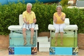 Senior couple on procedure for foot care — Stock Photo