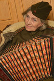 Elderly woman solder playing accordion — Stock Photo