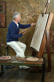 Elderly man painting with easel — Stock Photo